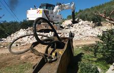 La màquina excavadora sobre les runes de la casa derruïda del matrimoni d'Alfara de Carles. Imatge del 20 de març de 2017 (horitzontal)
