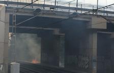 El foc crema els matolls del costat de les vies.