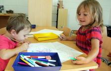 Primer pla de dues alumnes pintant a la nova escola de Mont-ral (Alt Camp), el primer dia de curs.