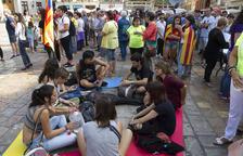 Un grup de joves assegut al terra de la plaça Mercadal