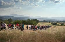 Un grup de centenars de refugiats amb hones, dones i nens camina camp a través a Europa, en un pla general.