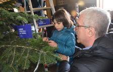 Josep Fèlix Ballesteros ayudando a colocar el mensaje a un niño.