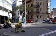 Un bomber recull restes de la terrassa que van quedar al mig del carrer després del despreniment d'ahir al matí.