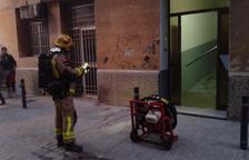 Un bomber, amb un ventilador a la porta de l'immoble.