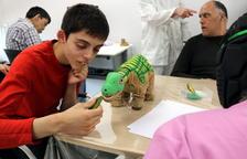 Un joven con trastorno mental interactuando con un peluche de dinosaurio, uno de los robots que ha adquirido el centro Villablanca, del grupo Pere Mata de Reus, para estimular a sus usuarios.