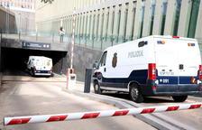 Plano medio desde detrás de dos furgonetas de la policía española entrando al parking subterráneo de la Ciudad de la Justicia, el 25-5-18