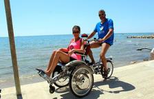 Una parella passeja prop de la platja amb una cadira-bicicleta adaptada OPair.