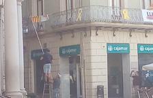 Imagen de los individuos sacando la pancarta sobre los presos políticos del Ayuntamiento de Reus.