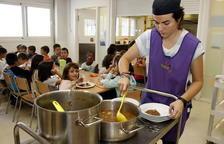 Una monitora servint menjar al plat al menjador escolar.