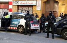 Imatge del moment en què la policia s'emporta detingut un noi del carrer Consell de Cent 596 arran de l'operació antiterrorista.