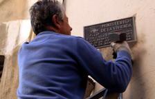 Un home que retira una de les set plaques franquistes despenjades, durant la segona acció de les entitats, de les façanes dels edificis dels carrers del centre de Tarragona.