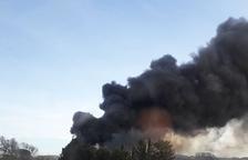 Cremen canyes i dues casetes de fusta darrere del Parc Riuclar