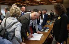 El senador electo de ERC Raül Romeva firmante un documento durante el trámite de recogida del acta de senador acompañado de otros senadores republicanos.