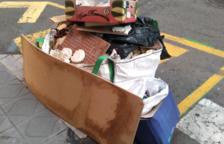 Una pila de brossa porta dos mesos en una vorera del carrer Eivissa