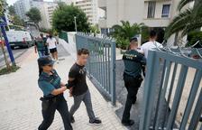 Los detenidos por una presunta agresión sexual en grupo en Benidorm entran custodiados en el edificio donde sucedieron los hechos.