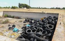 Els revestiments de les rodes dels vehicles estan apilats a la paret més pròxima al camí.