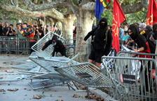 Un grup de manifestants llencen les tanques que protegeixen l'accés al Parlament.