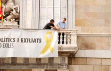 Dos treballadors de la Generalitat retiren la pancarta de la Generalitat després de l'ordre del TSJC