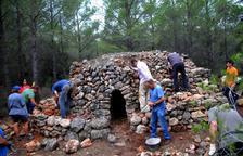 Voluntaris restauren una barraca de pedra seca a Mont-roig del Camp