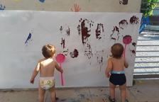 Dos niños pintando en una pared al jardín de infancia del Morell.