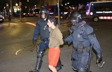 Plano medio de dos agentes y un manifestante detenido en la fuente del Centenari de Tarragona durante los disturbios en la ciudad.
