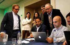 El número u de Vox per Barcelona, Ignacio Garriga, comentant els primers sondejos amb membres de la formació en una sala de l'hotel Hilton.