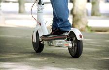 Primer plano de unos pies sobre un patinete eléctrico. (