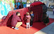 Dos niños hacen cagar un tió de grandes dimensiones a la plaza de los Infants.