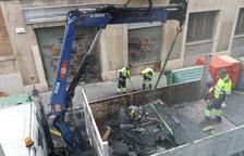 Operarios de limpieza retirando los contenedores quemados en la calle de la Selva del Camp.