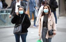 Dos mujeres con mascarillas andando|caminando por el centro de Barcelona
