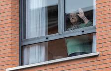 Una mujer saluda desde una residencia