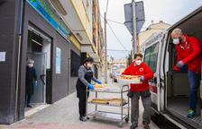 Dos miembros de Cruz Roja recogen alimentos para llevarlos al pabellón del Serrallo.