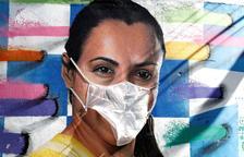 Un artista posa màscares a grafitis per a alertar de la COVID-19 al Brasil