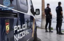 Agentes de la Policía Nacional al lado de un coche patrulla.