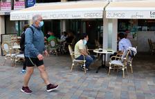 Plano general de la terraza de una cafetería en Calafell Platja mientras un hombre pasea con mascarilla.