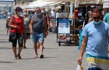 Plano general de personas paseando con mascarillas por la zona marítima de Calafell Platja.