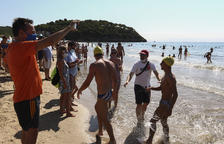 Uns nedadors són rebuts a l'arribada a la meta situada a la platja de la Móra.