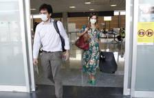 Dos pasajeros con mascarilla, saliendo del control de temperatura, a la terminal de llegadas del aeropuerto de Reus.