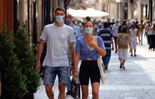 Un chico y una chica andando con mascarilla por la calle Monterols de Reus.
