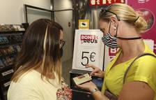 Dos mujeres consultan la web de los Bons Reus en su teléfono móvil.