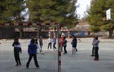 Niños jugando a fútbol durante la hora de recreo en el patio de la escuela.