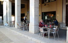 Pla general de la terrassa del bar La Tertúlia de Tortosa amb alguns clients.