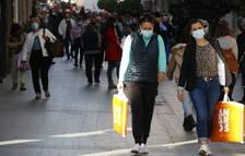 Unas chicas con bolsas, comprando en la calle de Llovera de Reus, en primer término, y en el fondo, gente paseando.