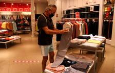 Un comprador mirando unos pantalones en una tienda del centro de Reus.