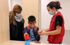 Fèlix, el niño que ha superado un cáncer de retina gracias a un tratamiento pionero en el mundo basado en la modificación genética de un virus, jugando al lado de su madre y de una voluntaria.