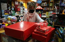 La presidenta presidenta de la Unió de Botiguers, Meritxell Barberà, entregant a una clienta regals embolicats, en el primer dissabte de la campanya de Nadal
