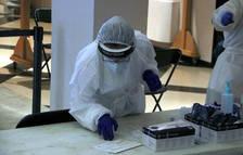 Una profesional analizando pruebas rápidas de covid-19 en el teatro de Figueres.