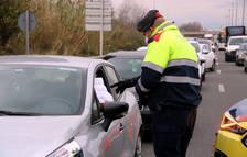 Un agent dels Mossos d'Esquadra comprovant el certificat que li mostra un conductor en un control de trànsit a la T-11, a Tarragona,