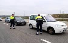 Dos agentes requiriendo la documentación a conductores parados en el control policial de la T-11 en Tarragona.
