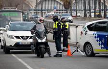 La Guardia Urbana de Barcelona habla con un motorista durante un control en la Ronda Litoral a raíz del confinamiento municipal.